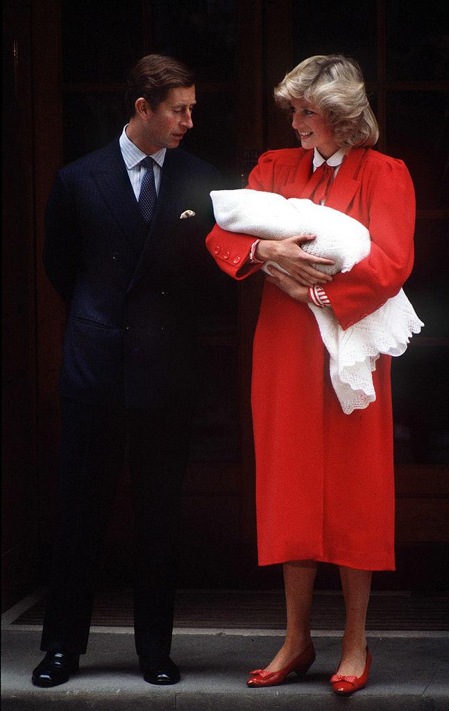 Prince Charles and Princess Diana holding Prince Harry