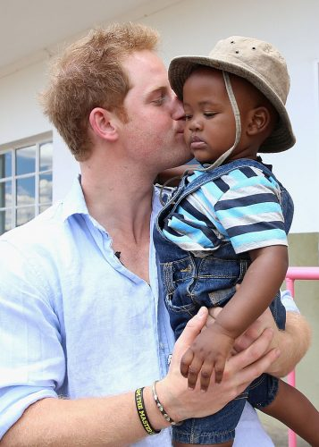 Prince Harry holds a child and kisses them on the cheek