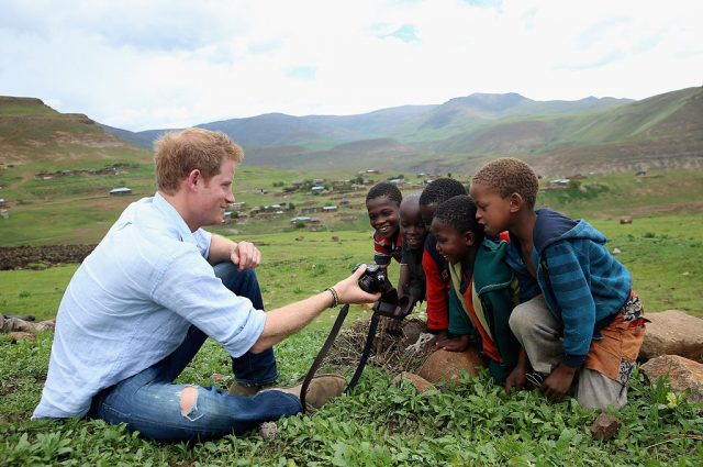Prince Harry shows kids a photo he took