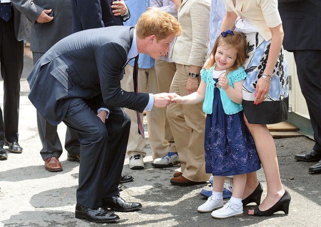 Prince Harry shakes a young girl's hand