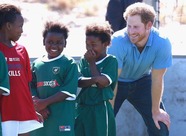 Prince Harry smiles standing next to three girls while they laugh
