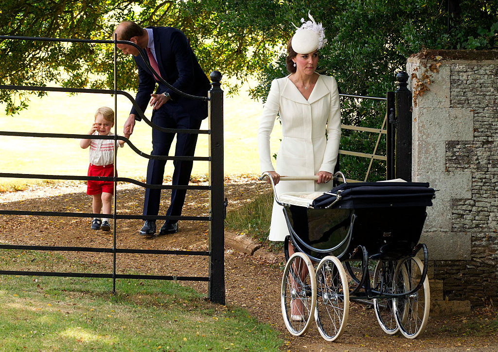 Prince William walks with Prince George while Kate Middleton pushes Princess Charlotte in a stroller