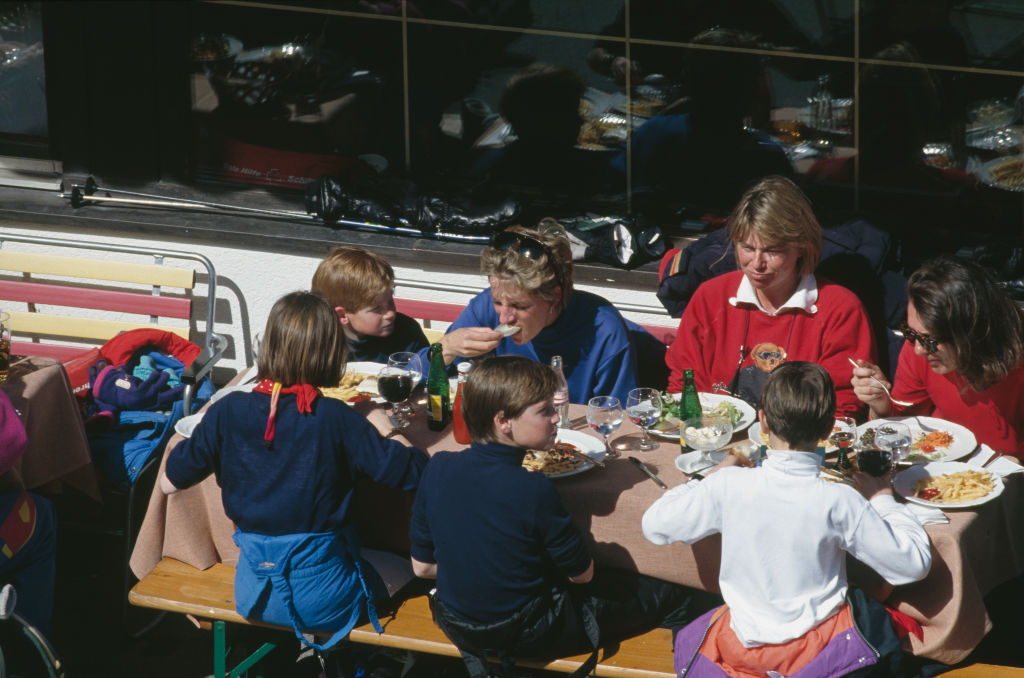 Princess Diana, Prince Harry, and Prince William having lunch with friends on a ski trip