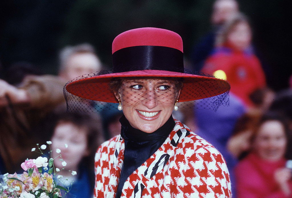 Diana, Princess Of Wales, Smiling On A Walkabout After Attending Christening Service At Sandringham Church. The Princess Is Wearing A Houndstooth Red And White Jacket Designed By Moschino With A Black Polo Neck Jumper And A Broad-brimmed Red Hat.