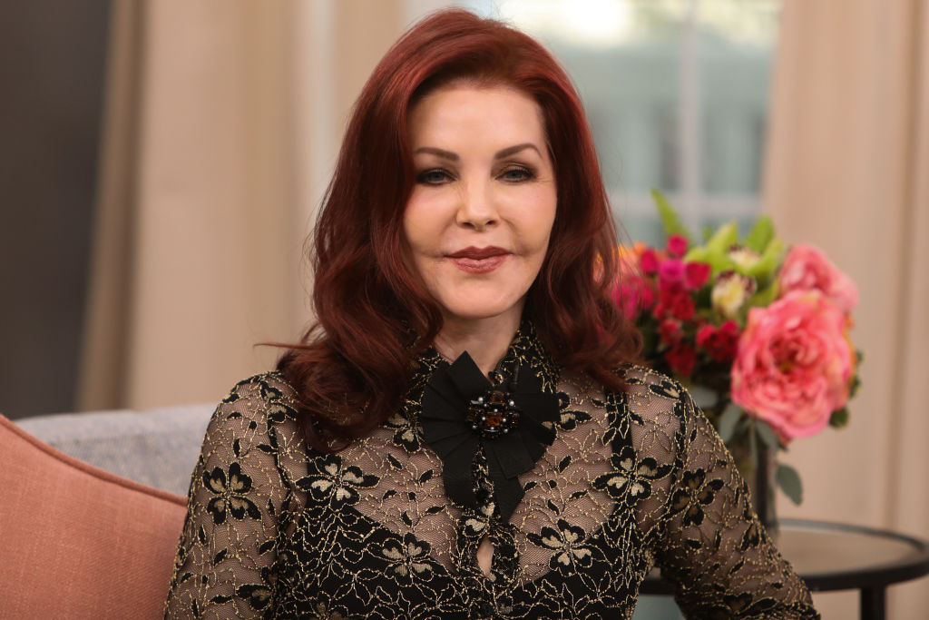 Priscilla Presley smiling on a talk show style couch