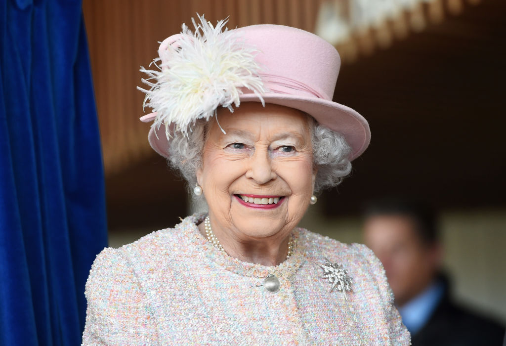 Queen Elizabeth II smiling in a pink hat