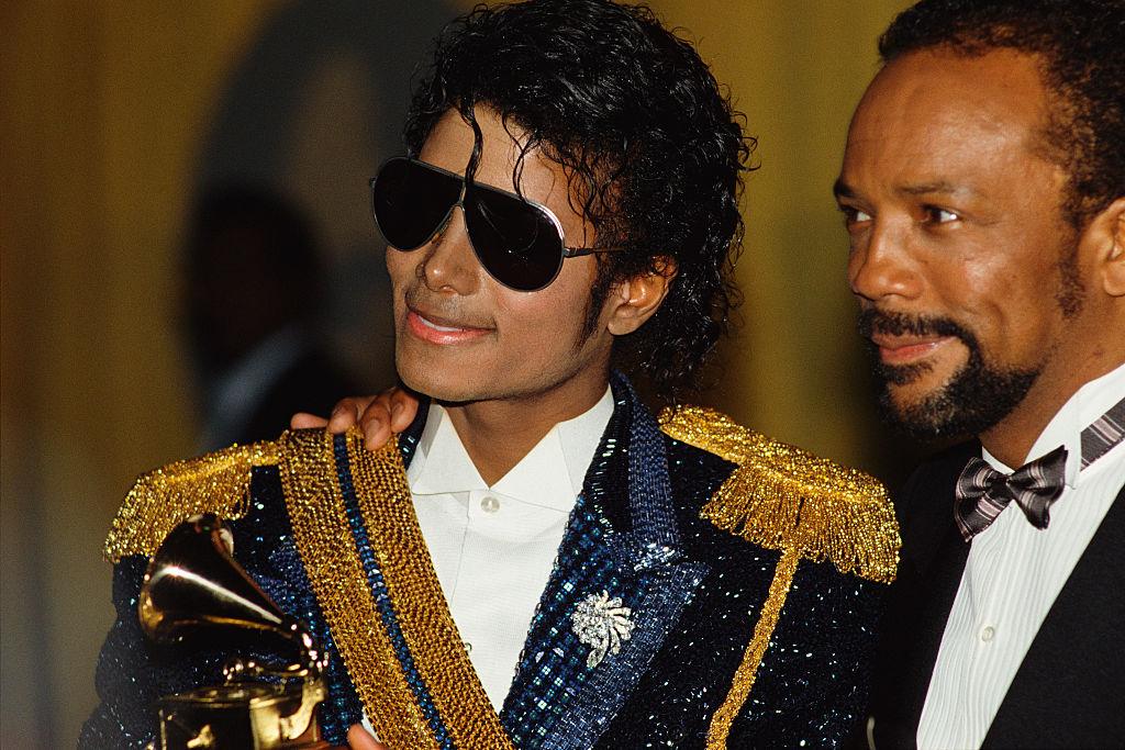 "Quincy Jones in a suit next to Michael Jackson, the singer of ""Billie Jean"""