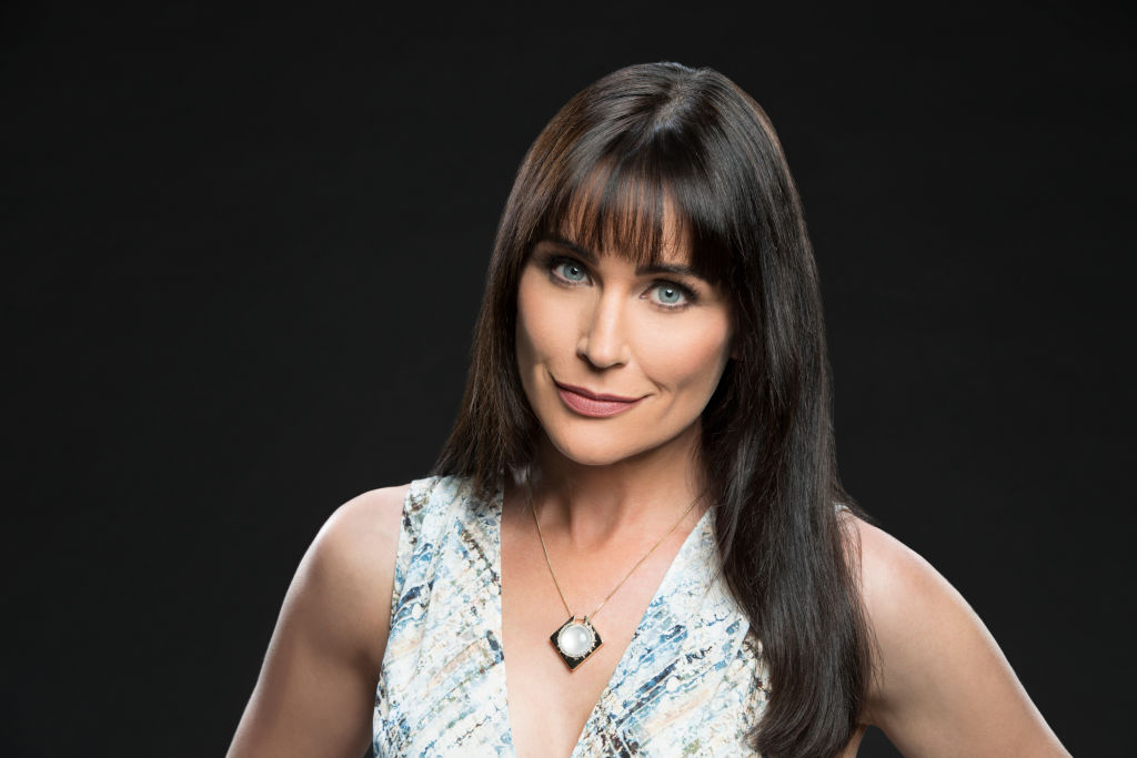 Rena Sofer smiling in front of a gray background