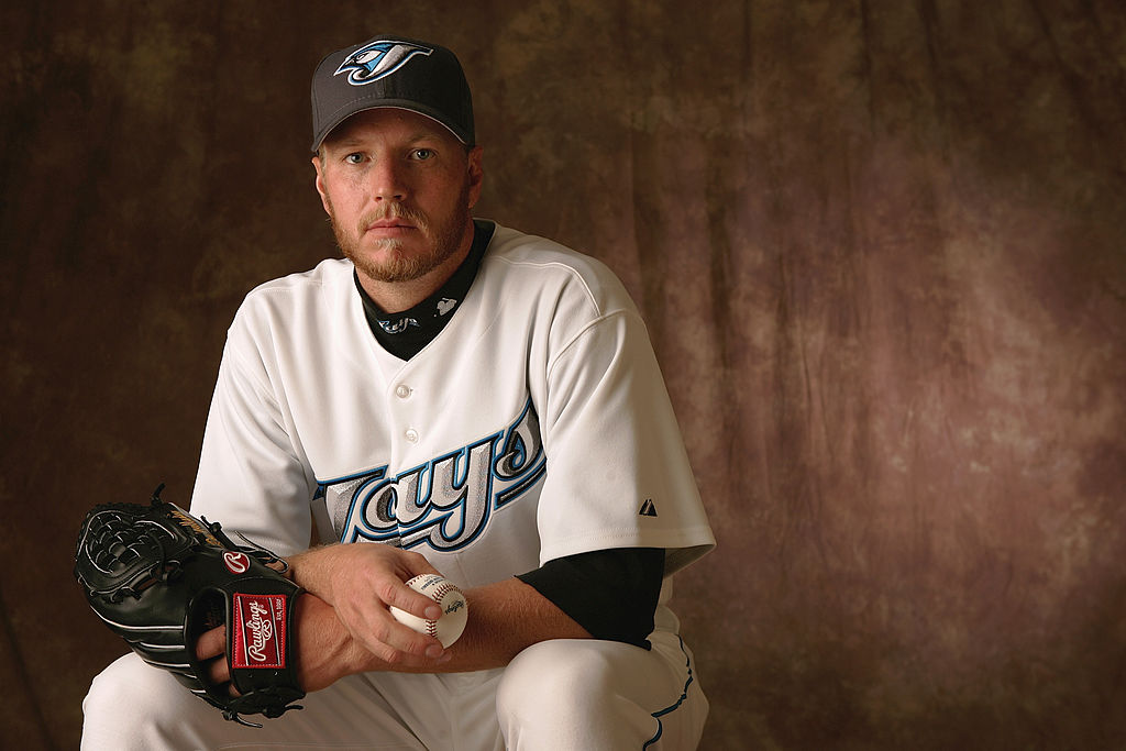 Roy Halladay in Toronto Blue Jays Uniform seated in front of a textured brown background