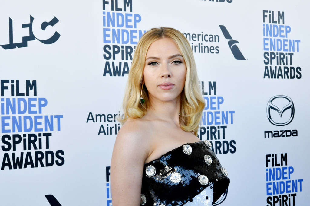 Scarlett Johansson smiling in front of a repeating background