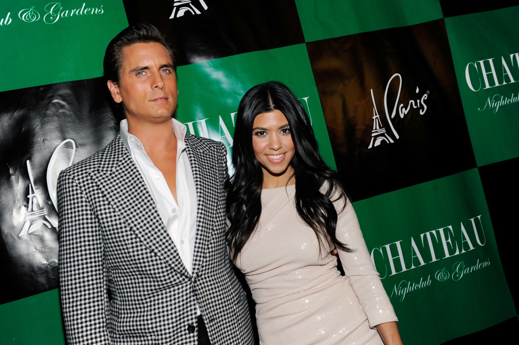 Scott Disick and Kourtney Kardashian smiling in front of a repeating background