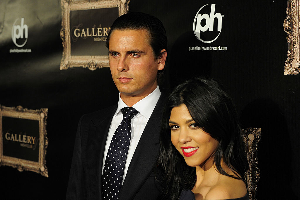 Scott Disick and Kourtney Kardashian in front of a repeating background