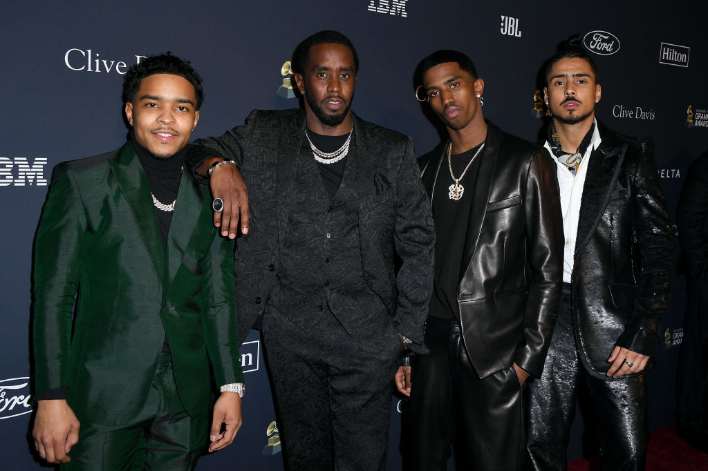 """Justin Dior Combs, Honoree Sean """"Diddy"""" Combs, Christian Casey Combs, and Quincy Taylor Brown in front of a repeating background"""