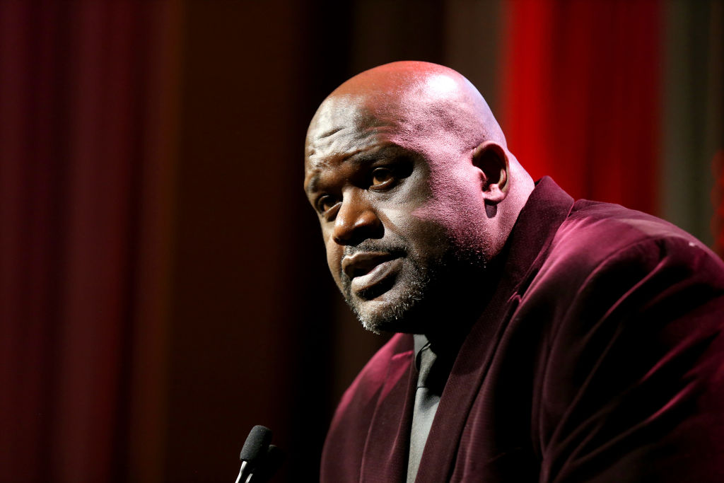 Shaquille O'Neal at a podium in a dark red jacket