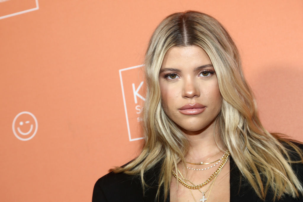 Sofia Richie looking into the camera in front of an orange background