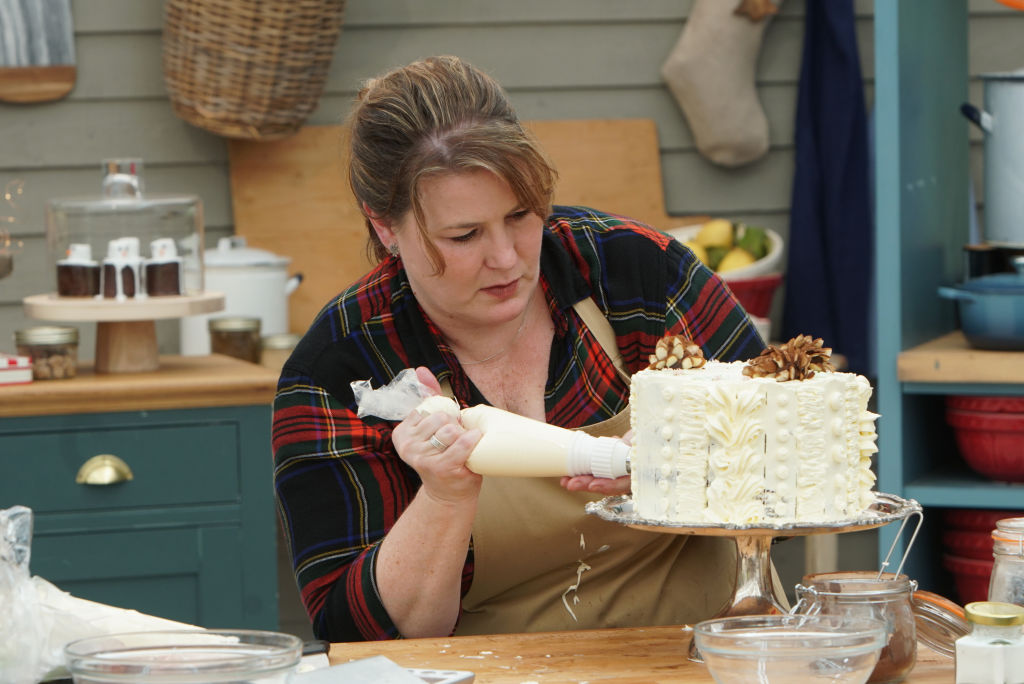 A contestant on 'The Great American Baking Show: Holiday Edition 2019' decorates a cake