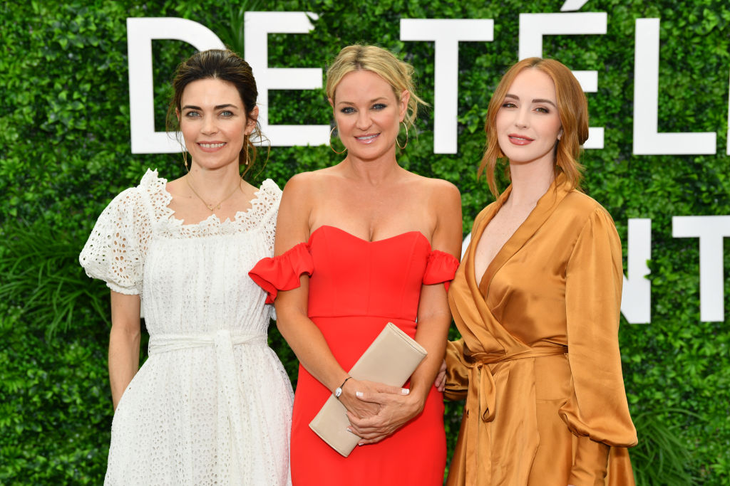 Amelia Heinle, Sharon Case and Camryn Grimes smiling in front of a green background