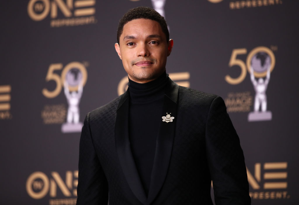 Trevor Noah in front of a repeating background