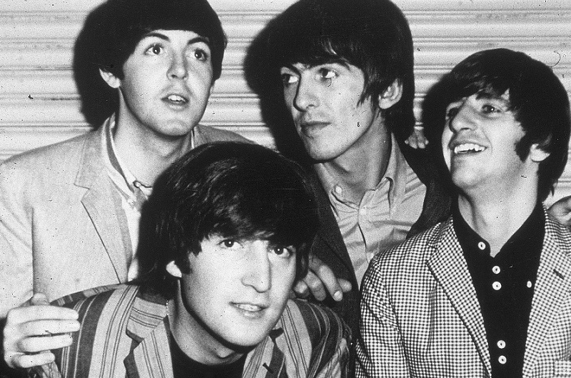 The Beatles smile for the camera in 1965.