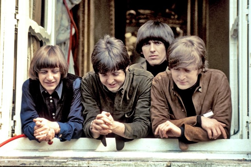 The Beatles stand at a window while filming 'Help'
