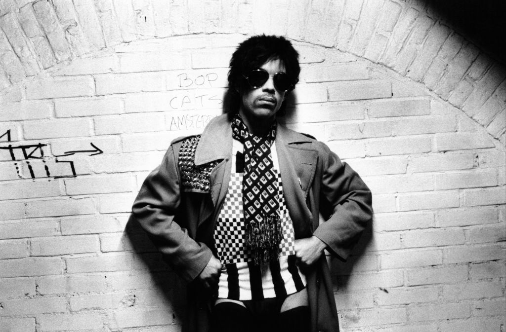 Prince leaning on a wall
