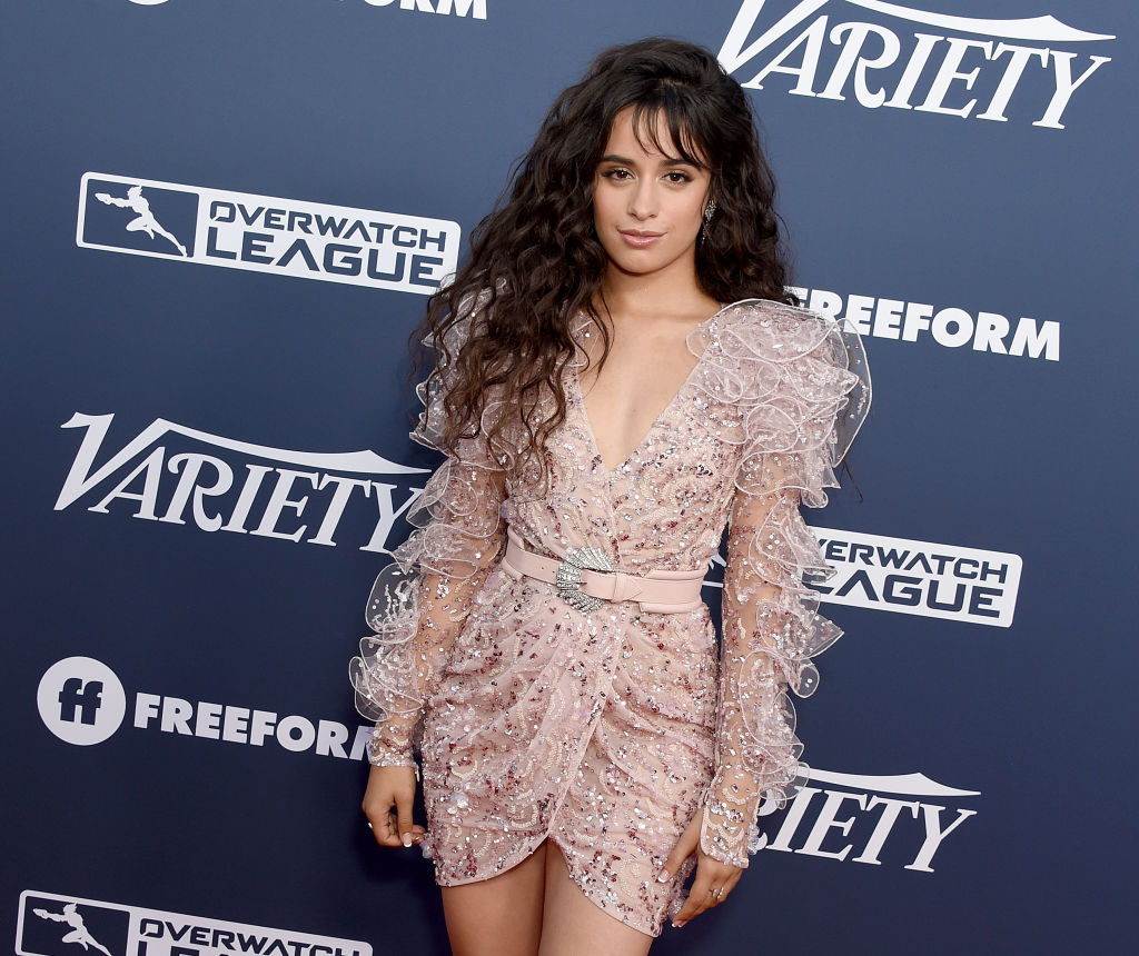 Camila Cabello in a sparkly, glittery outfit with a black background
