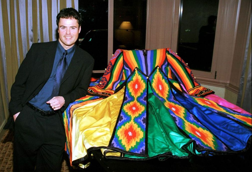 "Donny Osmond poses next to the ""Dreamcoat"" during a reception for the Universal Studios Home Video release of 'Joseph and the Amazing Technicolor Dreamcoat,' February 13, 2000."