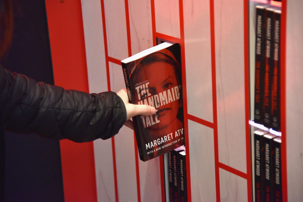 Person removes copy of The Handmaid's Tale from a shelf