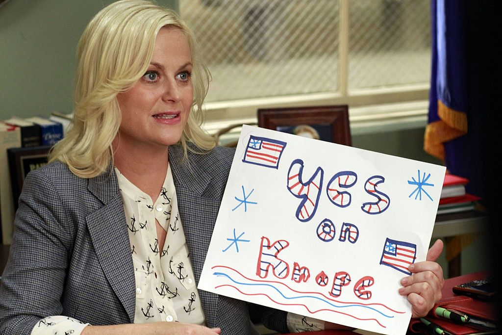 "Amy Poehler as Leslie Knope holds up a sign that reads, ""Yes on Knope,"" in 'Parks and Recreation' Season 4."