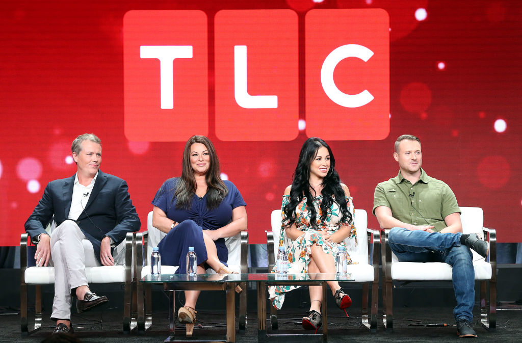 Matt Sharp, Molly Hopkins, Paola Mayfield, Russ Mayfield of the television show '90 Day Fiance' smiling on a stage