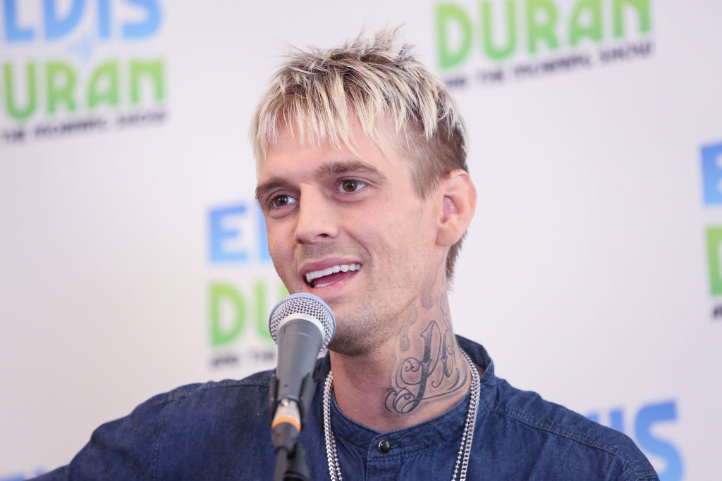 Aaron Carter in front of a microphone in front of a repeating white and blue background