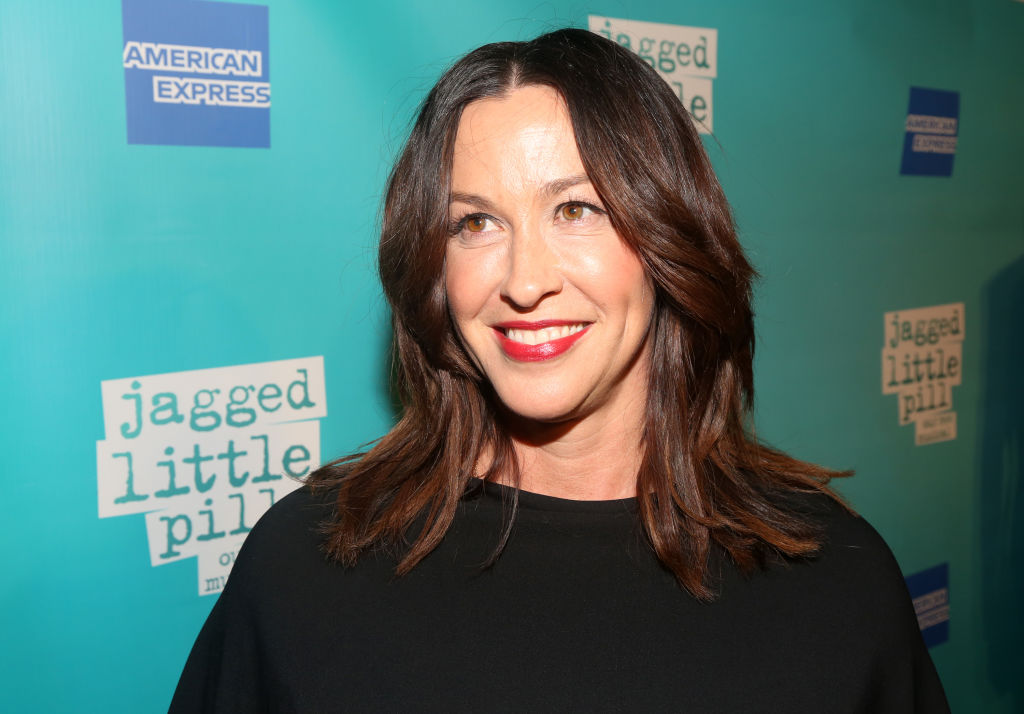 Alanis Morissette smiling turned slight away from the camera in front of a blue repeating background