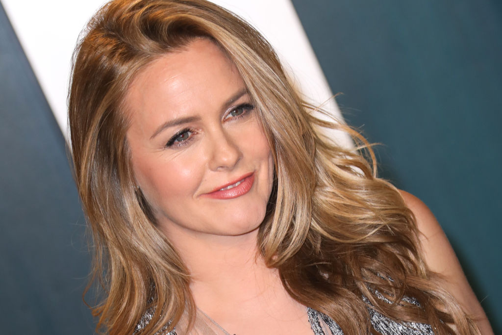 Alicia Silverstone smiling in front of a white and blue backdrop