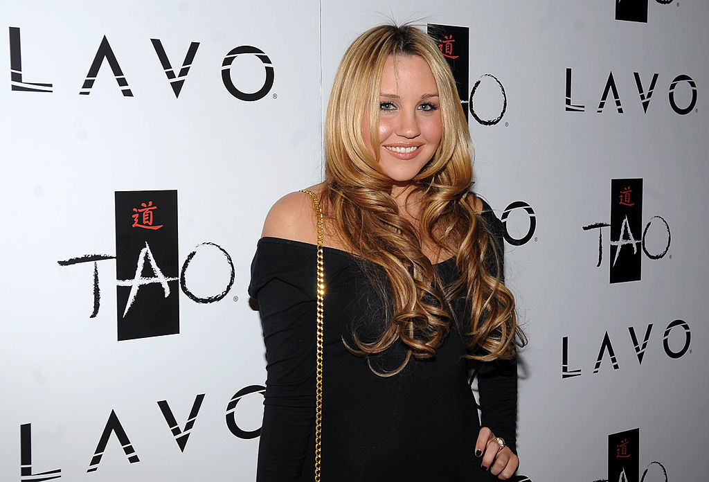 Amanda Bynes smiling in front of a white background with a repeating logo