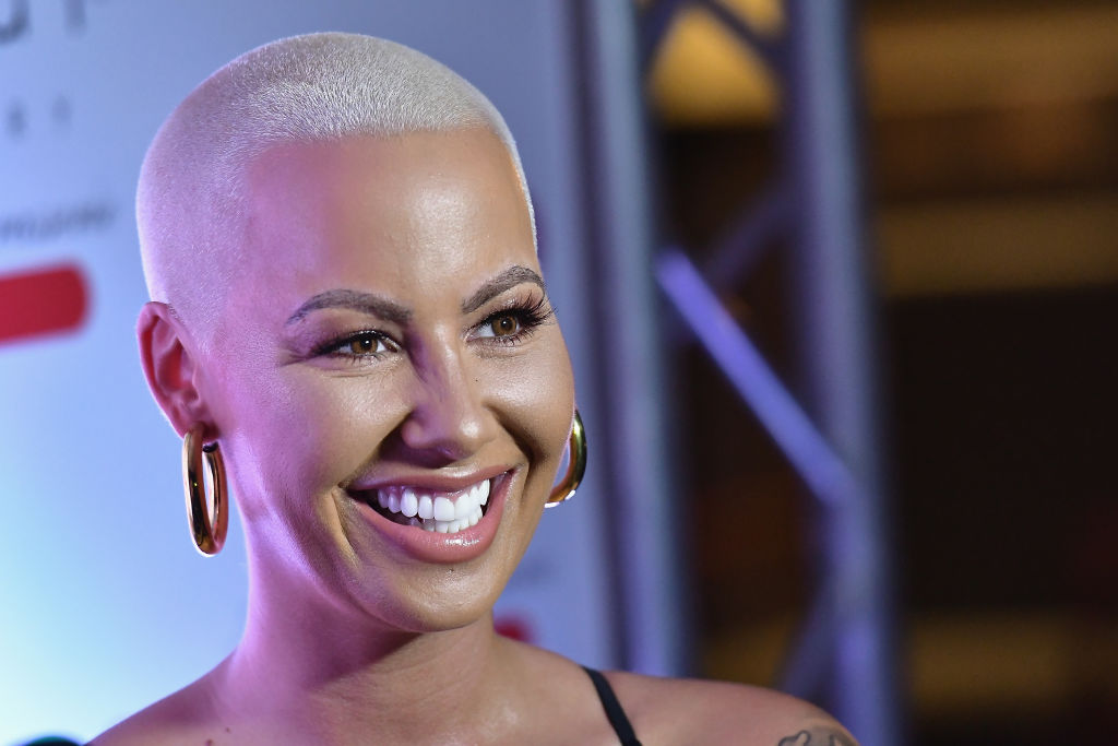 Amber Rose smiling in front of a repeating background