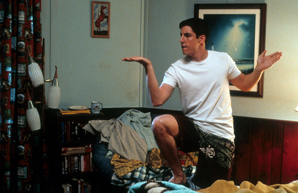 Jason Biggs dancing around on messy bed in a scene from the film 'American Pie 2'