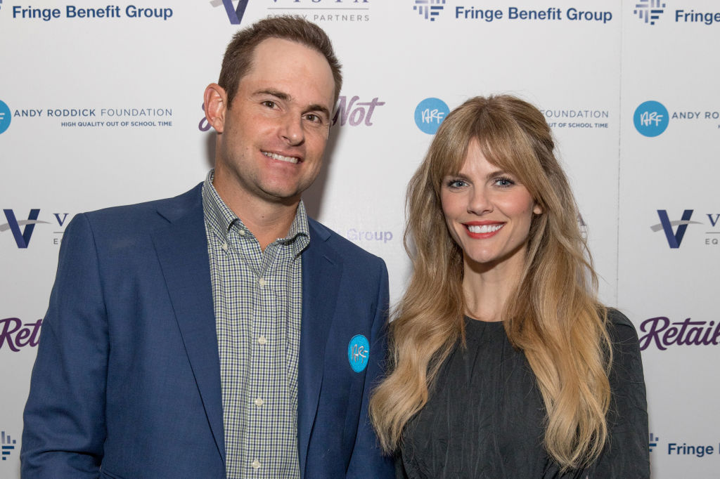 Andy Roddick and Brooklyn Decker smiling in front of a repeating background