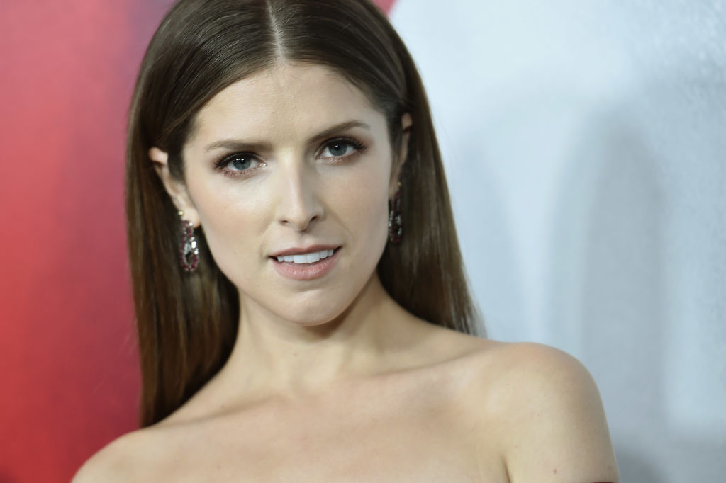 Anna Kendrick smiling at the camera in front of a red and white background