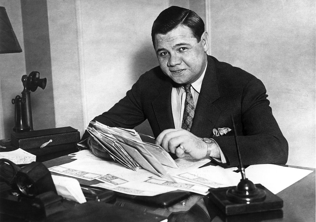 Babe Ruth smiling while opening letters, image in black and white