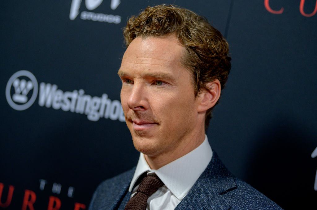 Benedict Cumberbatch looking away from the camera standing in front of a repeating background