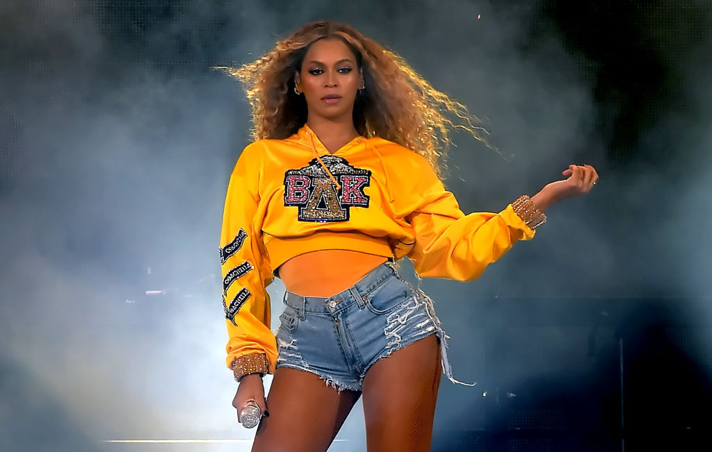 Beyoncé on stage in a yellow cropped sweatshirt and denim shorts
