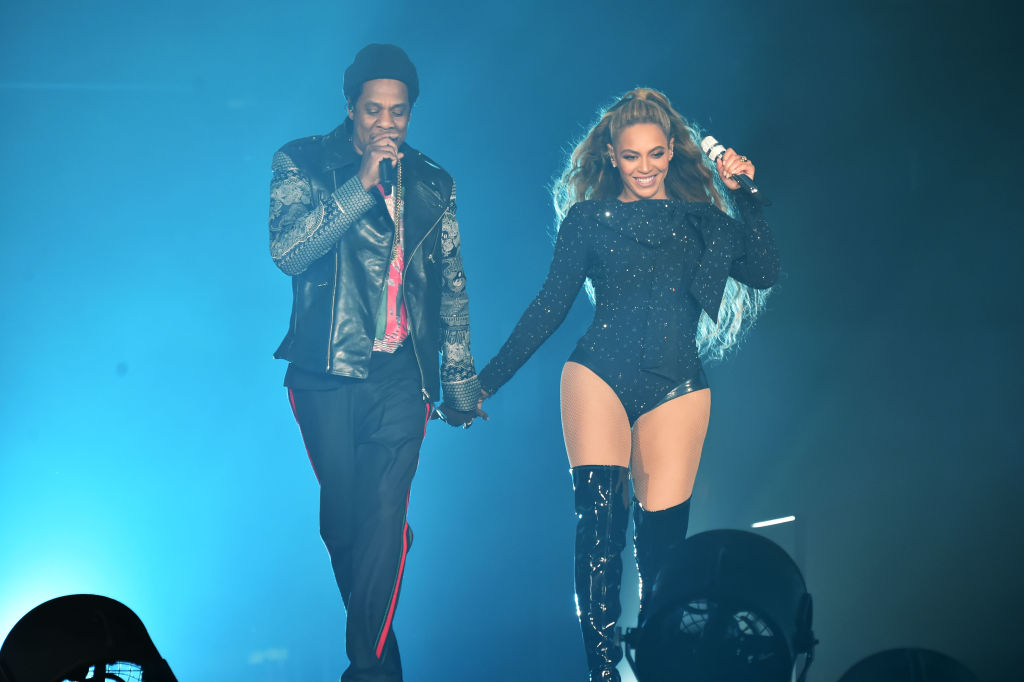 Beyonce and Jay-Z on stage holding hands while performing