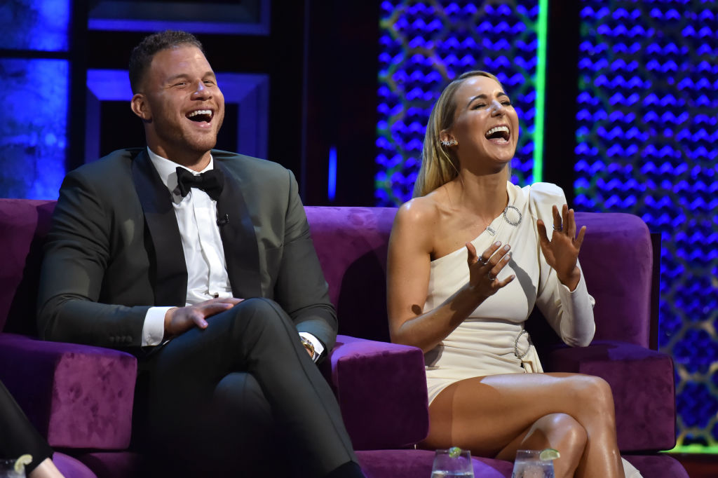 Blake Griffin and Nikki Glaser sitting next to each other on stage laughing