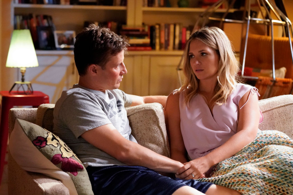 Will Estes as Jamie Reagan in profile, seated on a couch, looking at Vanessa Ray as Eddie Janko while talking