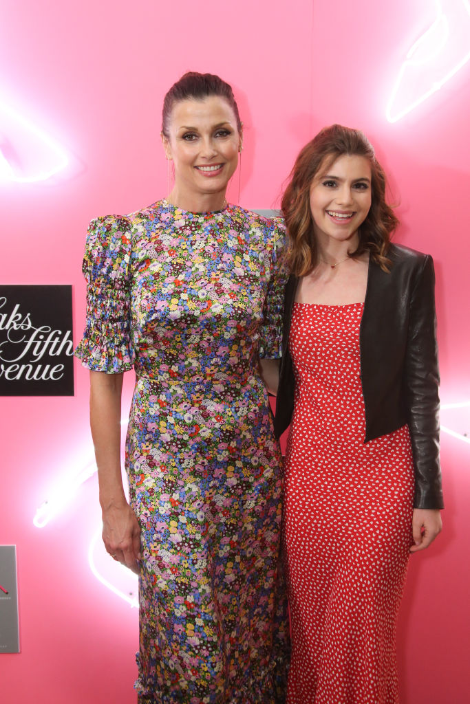 Bridget Moynahan and Sami Gayle smiling in front of a pink background