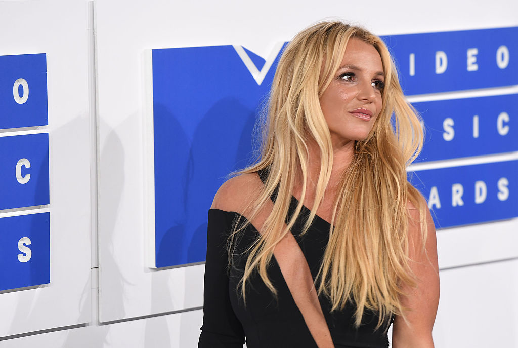 Britney Spears smiling, turned away from the camera in front of a blue and white backdrop