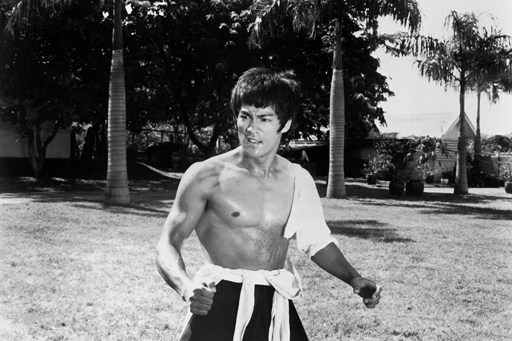 Bruce Lee looking away from the camera, shirtless, with his arms slightly outstretched
