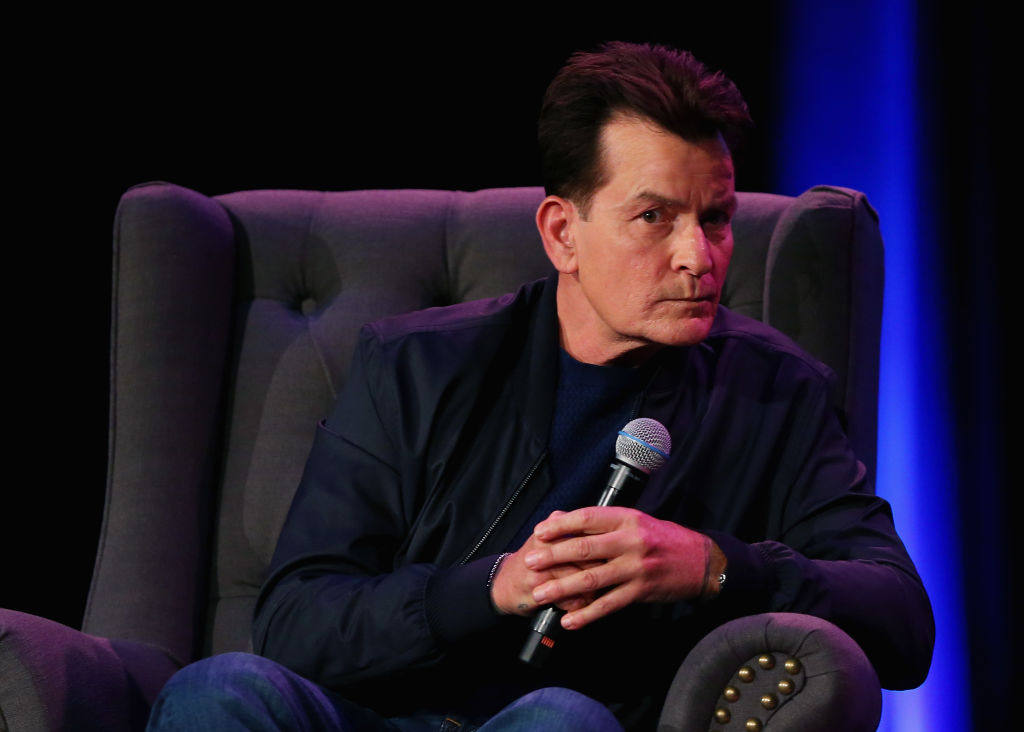 Charlie Sheen sitting in a chair holding a microphone looking away from the camera