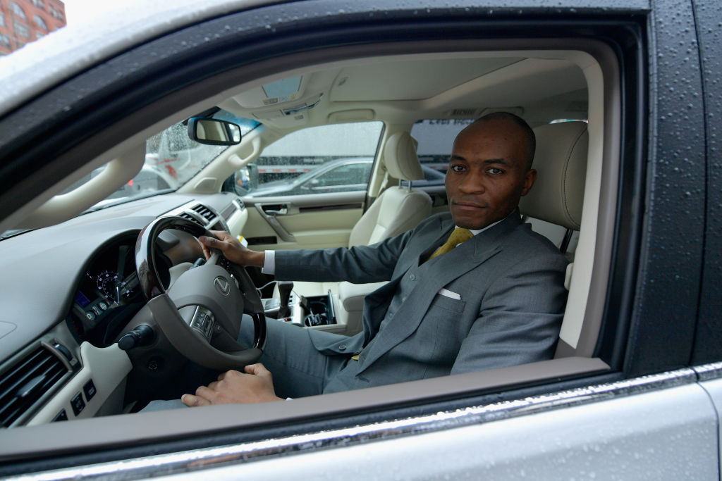 A chauffeur in a gray suit looking out the window of a car at the camera