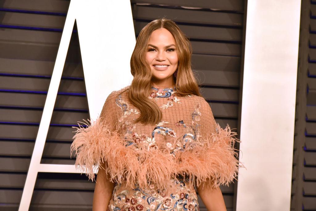 Chrissy Teigen smiling in a pink dress
